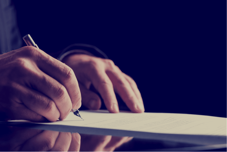 Close up of hands signing a will