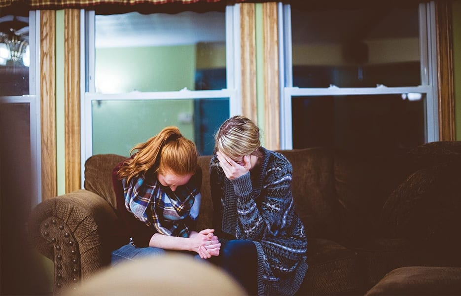 Mother and daughter sitting on sofa in a room, looking worried