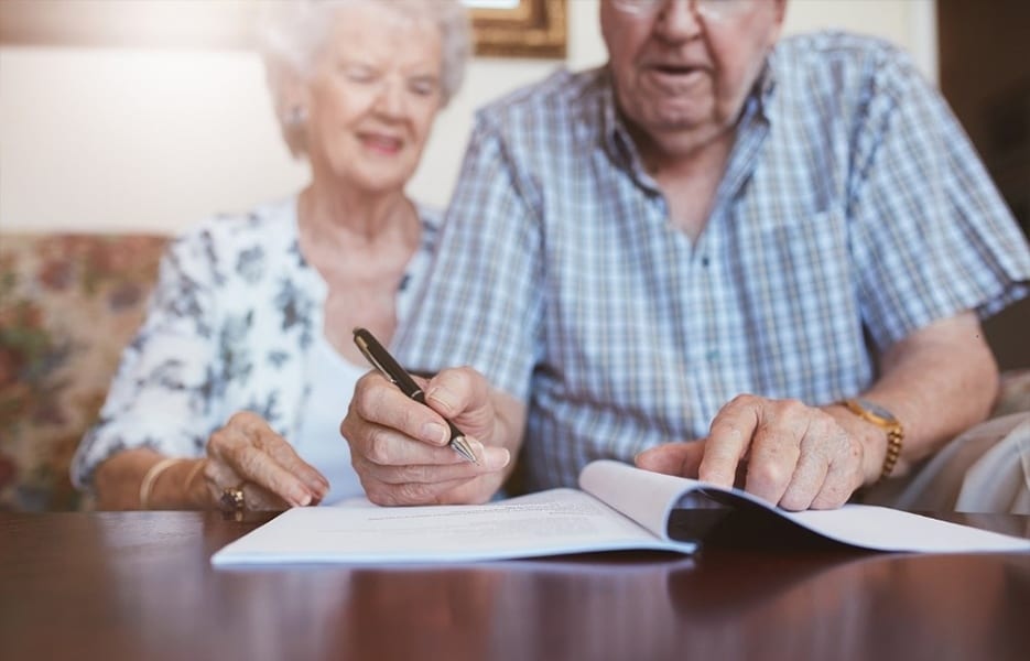 Elderly Caucasian man and woman sitting at home and signing some paperwork.