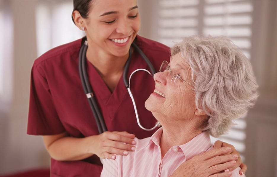 Female nurse looking and smiling with senior Caucasian woman at a rest home