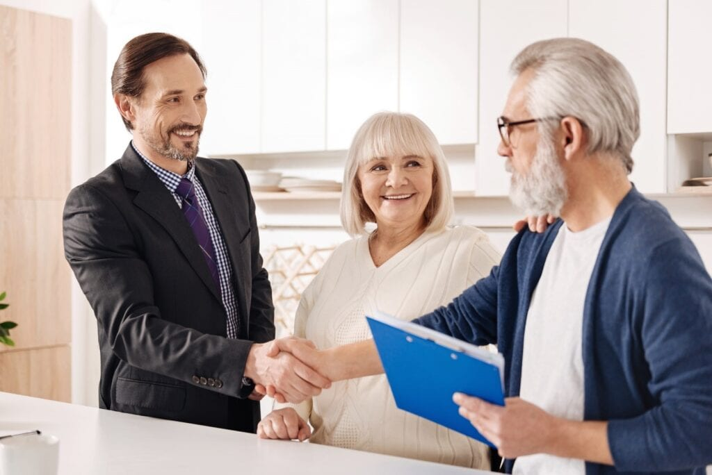 Elderly couple shaking hands with legal advisor and smiling