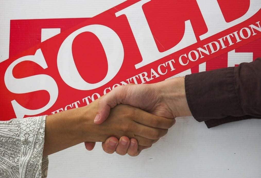 Two hands shaking in front of a sold property sign